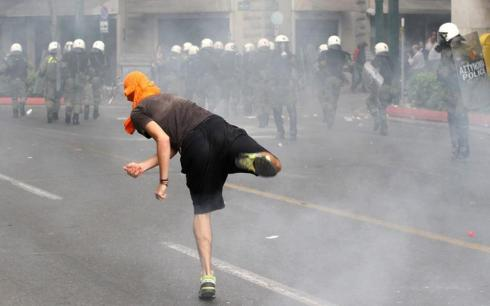 Protesters clash with riot policemen in front of the Parliament building in Athens.