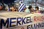 Protesters hold a banner reading Merkel Out during an anti-austerity demonstration in front of the Greek parliament